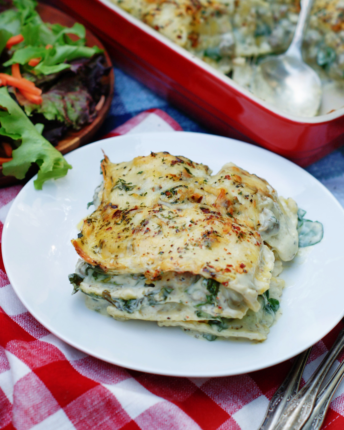 white ravioli casserole with alfredo sauce, spinach and sausage in an easy casserole