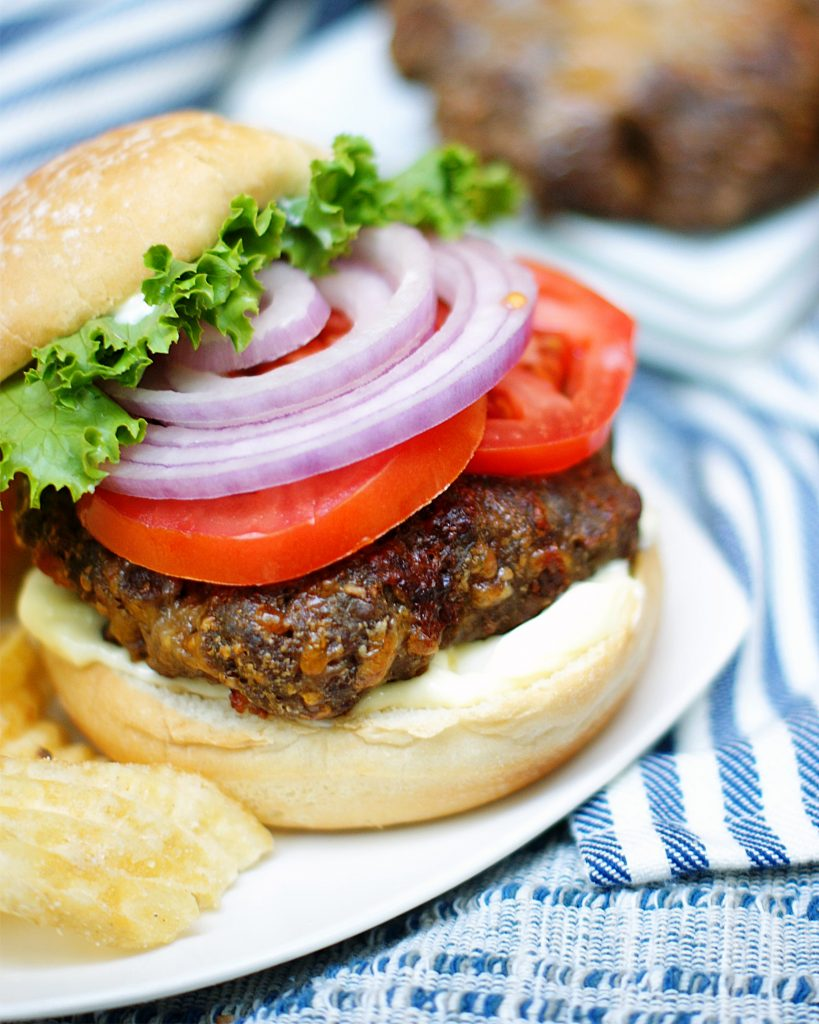 Juicy Lucy Broiler Burger with lettuce, tomato and red onion.