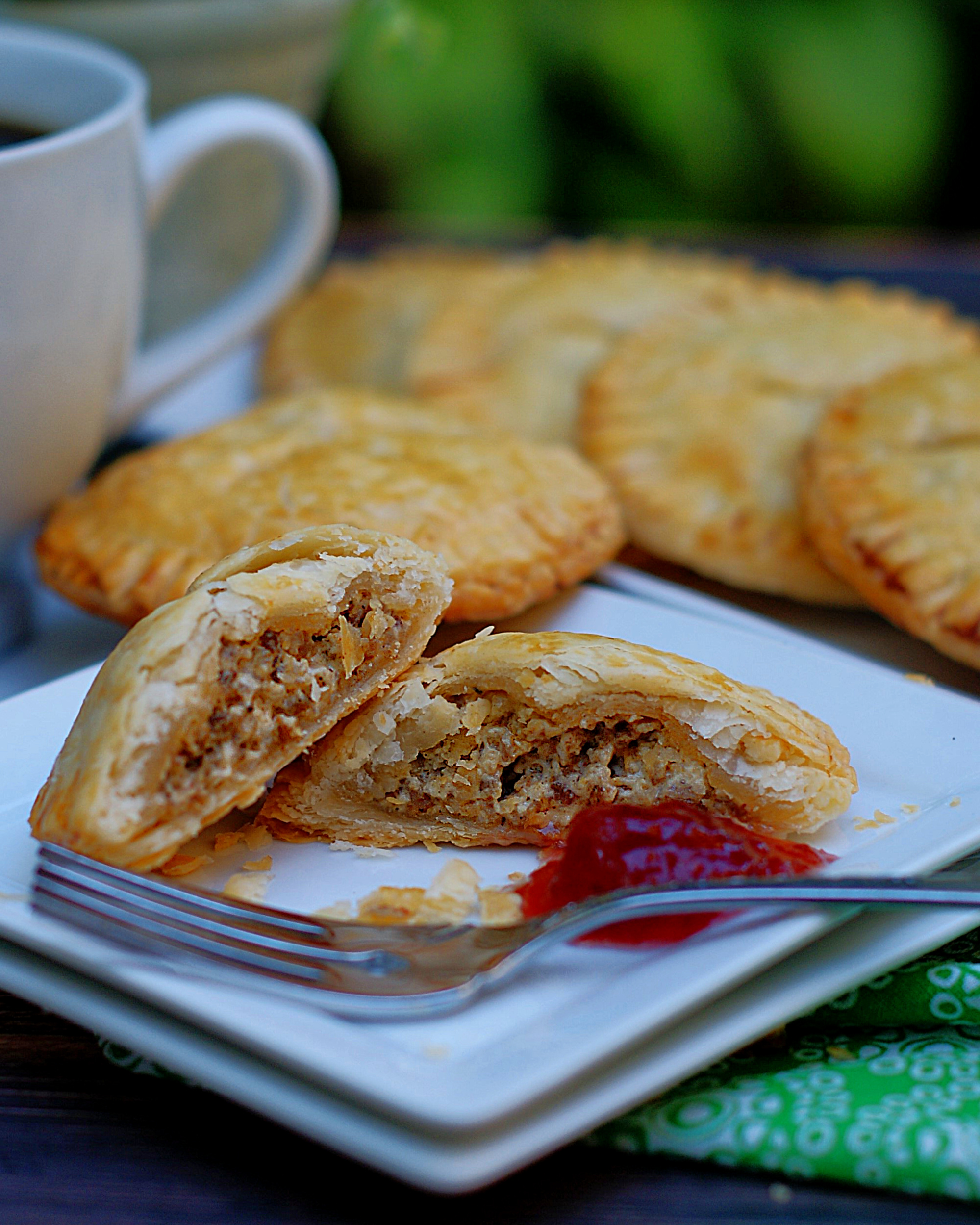 An up close of a cut sausage & cream cheese hand pie with jam.