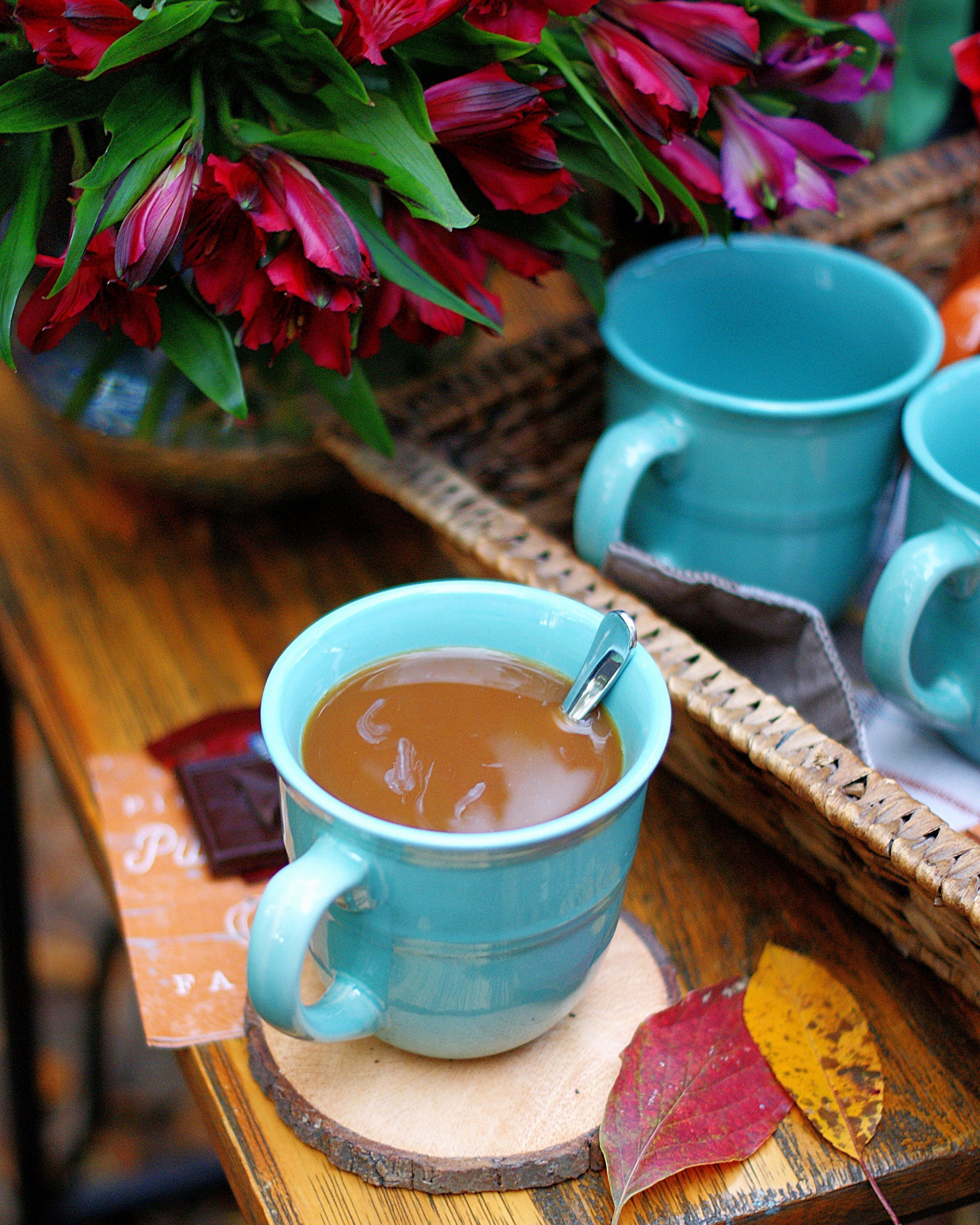 A cozy cup of coffee with fall leaves and chocolate square.