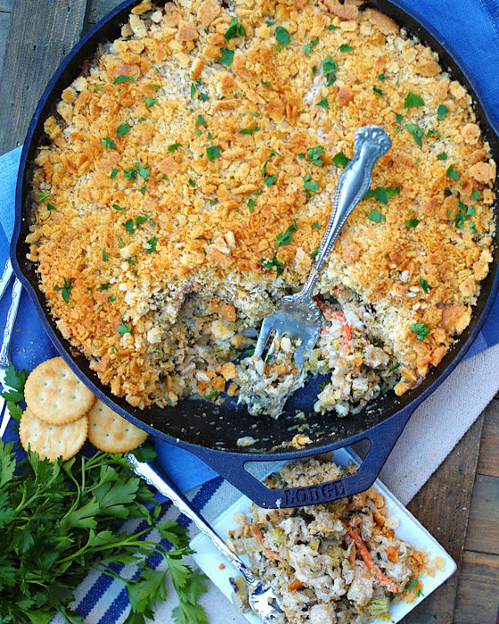Chicken & Wild Rice Casserole in a cast iron skillet with serving fork.