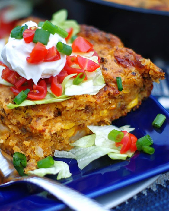 Upclose of a slice of Mexican Cornbread topped with lettuce and tomatoes.