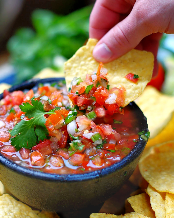 dipping fresh salsa with tortilla chips