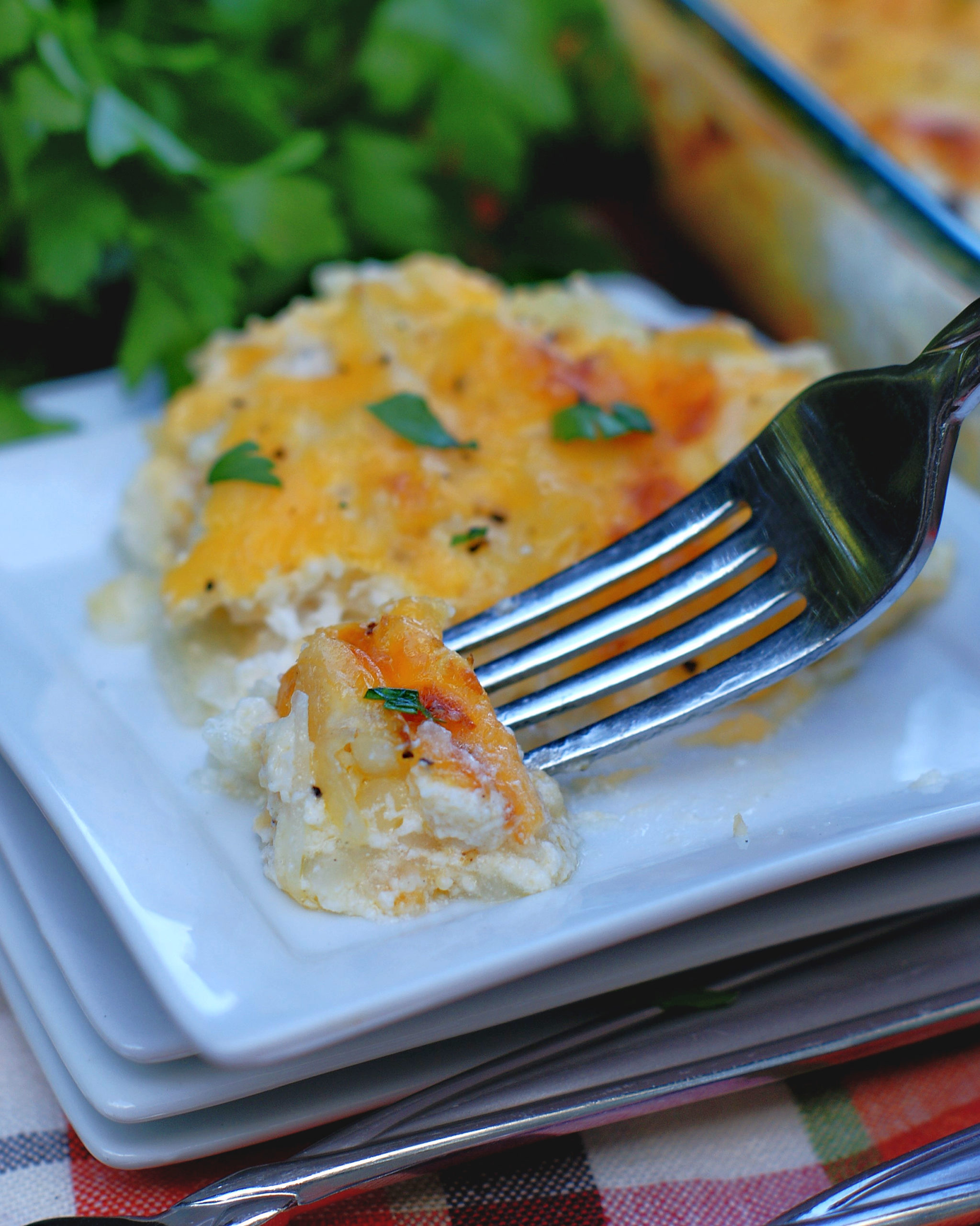 Cheesy Hashbrown Casserole on a plate with a fork