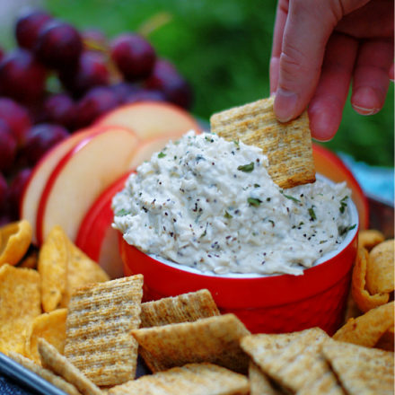 Dipping Creamy Peppercorn Parmesan Cheese Dip with a cracker