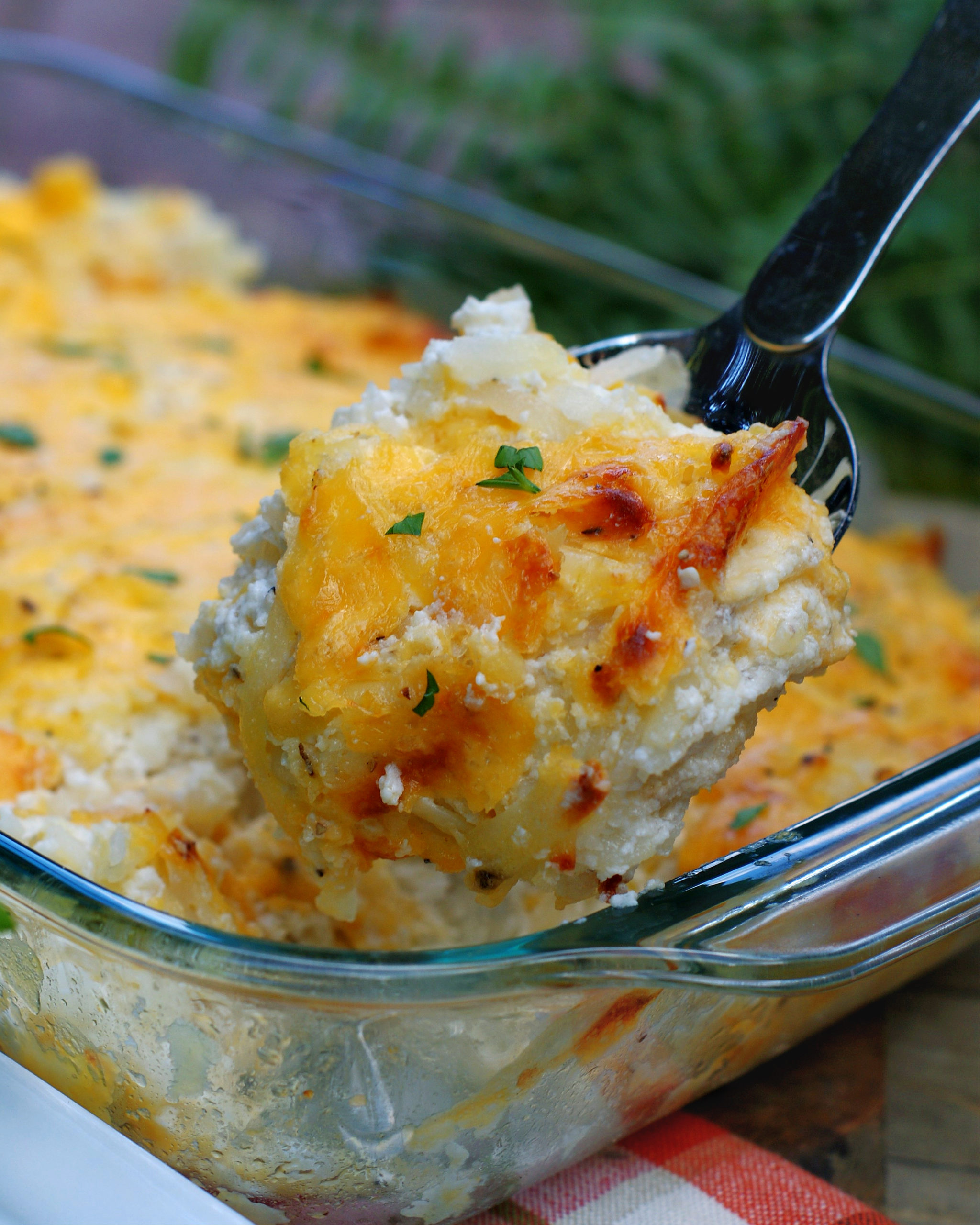 A serving of Cheesy Hashbrown Casserole in a spoon
