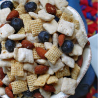 A close up of blueberry muddy buddy snack mix in a white bowl