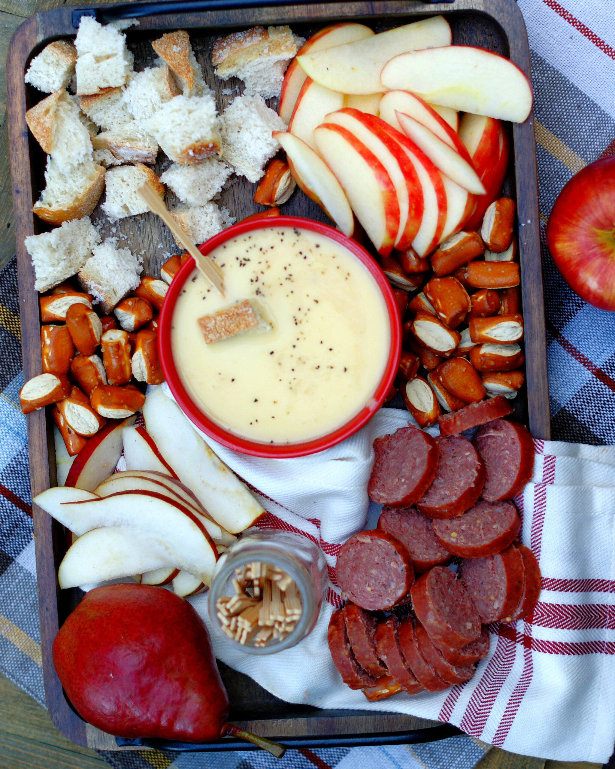 Easy Apple Cheese Fondue on a tray with a variety of dippers
