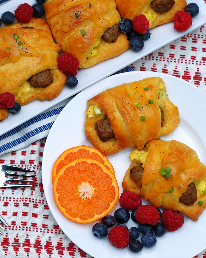 Sausage Egg Crescent Rolls on a plate with fruit