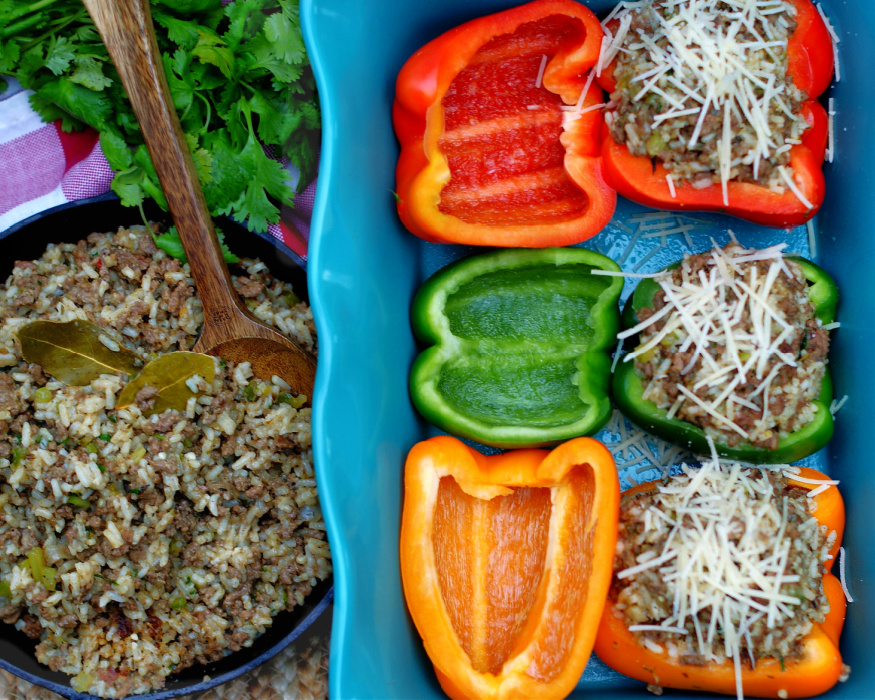 The process of stuffing Louisiana Dirty Rice bell peppers topped with Parmesan cheese