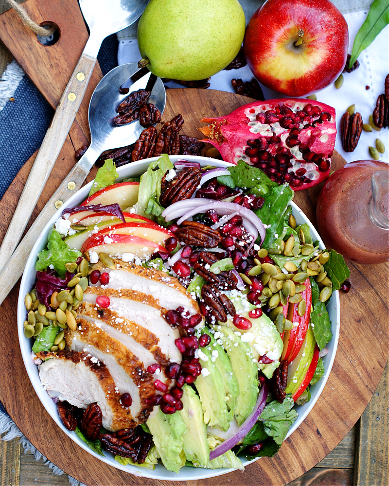 An overhead photo of apple pear pomegranate salad with chicken and avocado