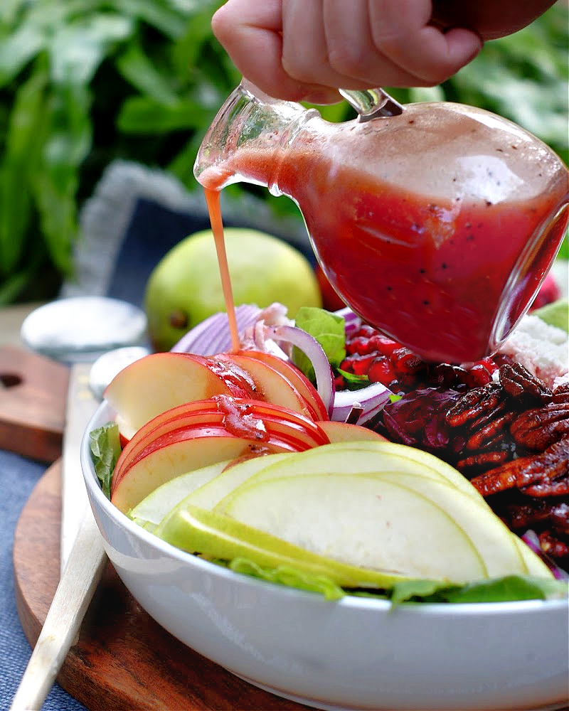 pomegranate vinaigrette drizzling over a salad.