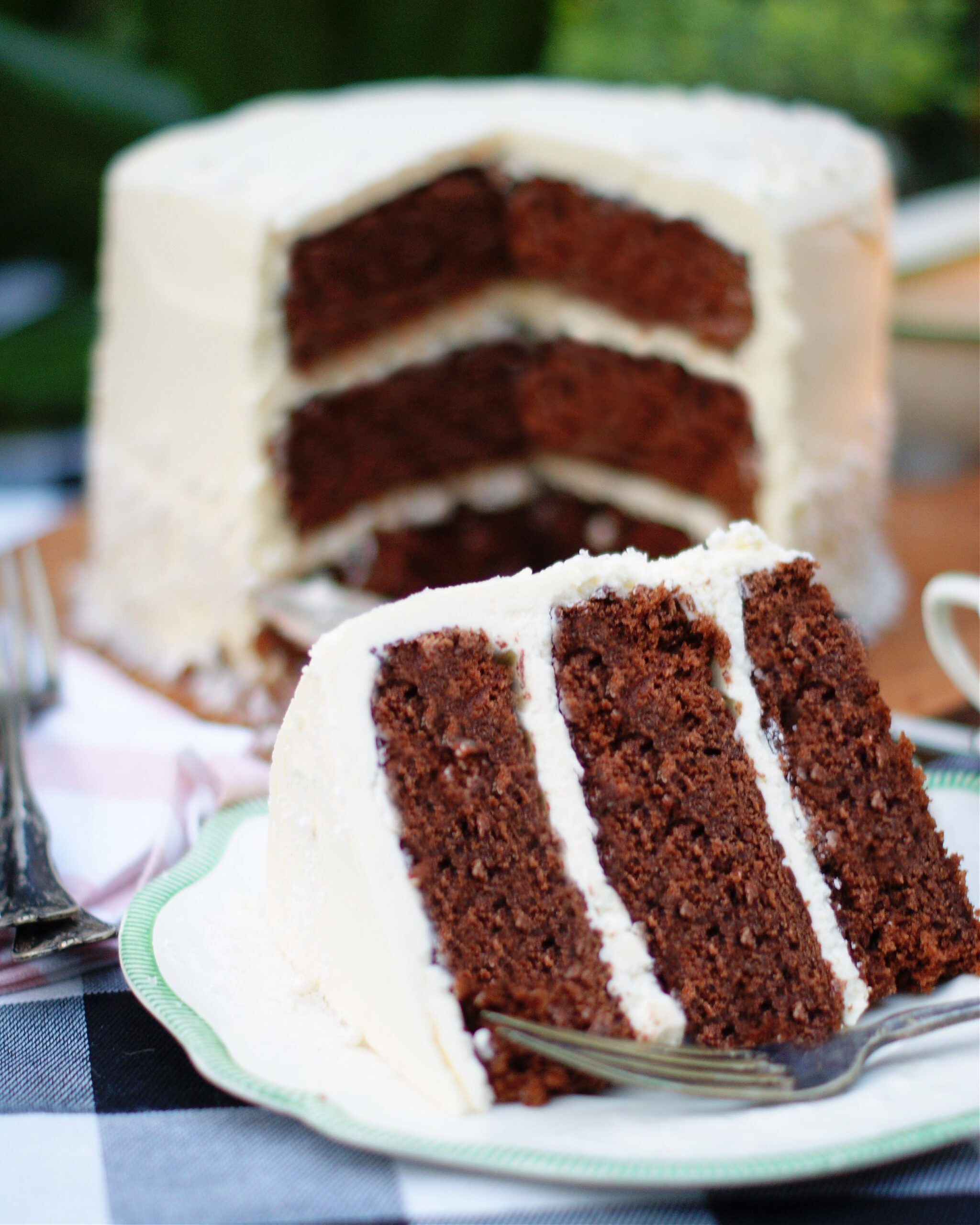 A large slice of dark chocolate layer cake with white chocolate buttercream with the cake in the background.