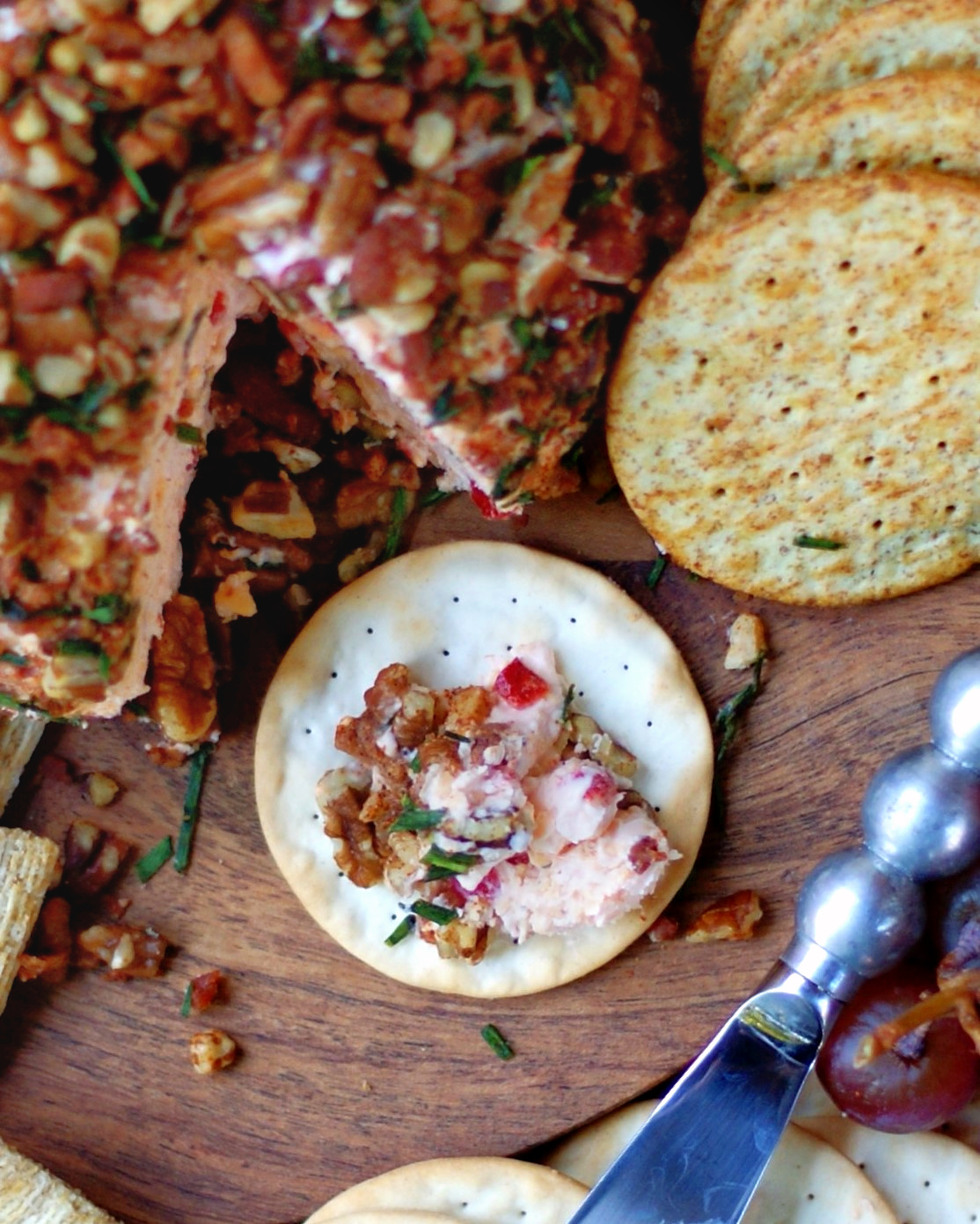Pimento cheese ball with pecans, cream cheese and bacon being served
