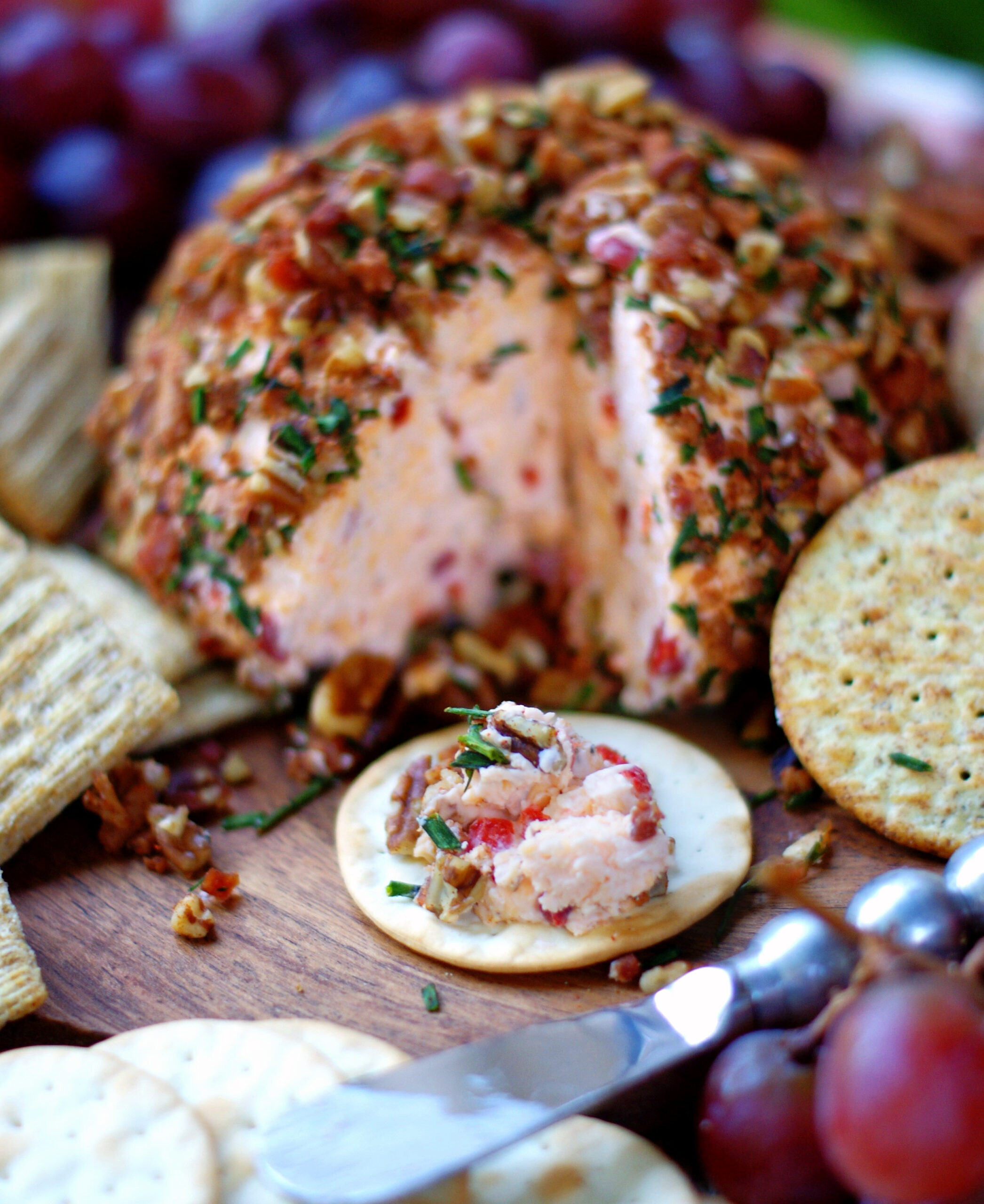 Pimento Cheese Ball made with cream cheese and served on a cracker.