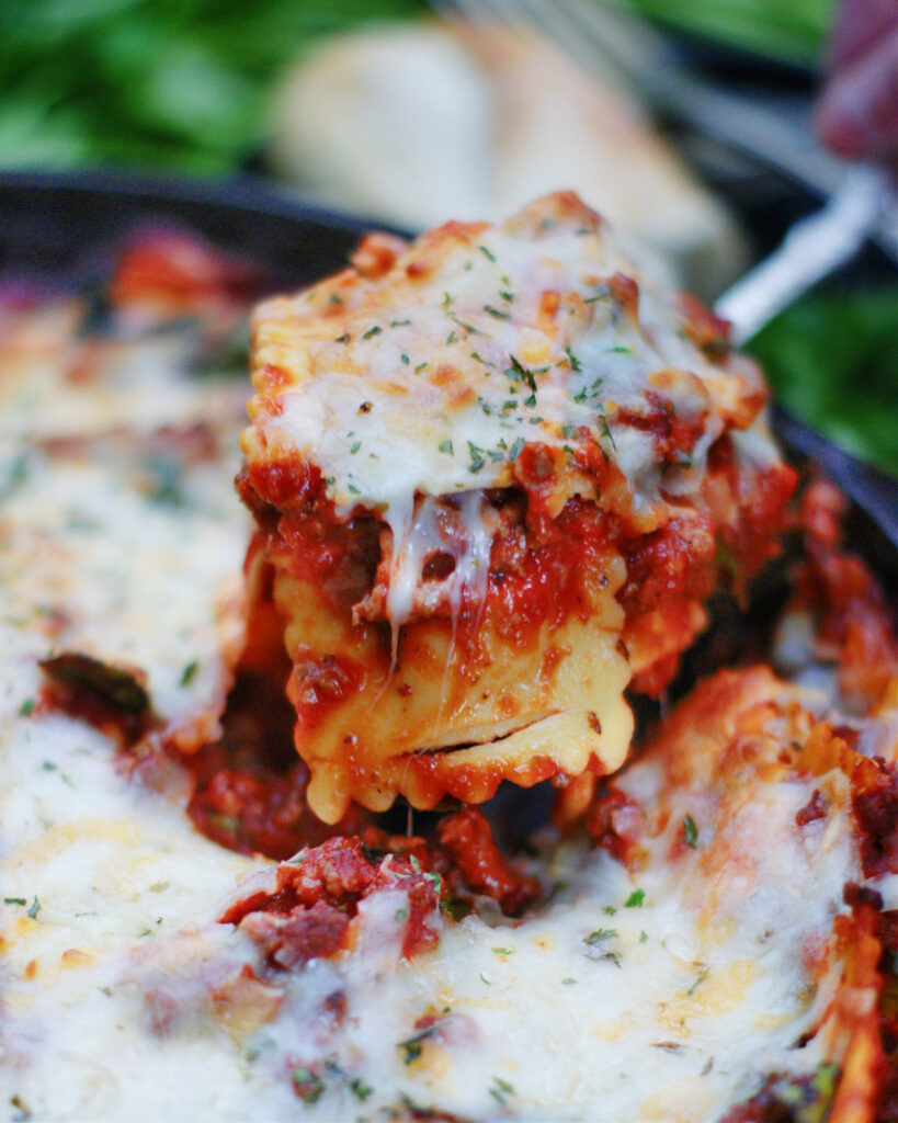 Serving a spoonful of baked ravioli with meat sauce.