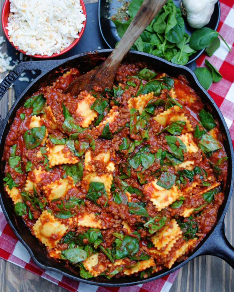 One dish baked ravioli with tomato beef sauce and spinach