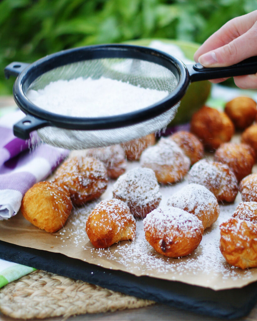Generously dust beignets with powdered sugar for a sweet topping.