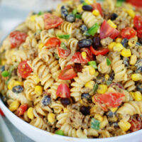 Tex Mex Pasta Salad is loaded with seasoned ground beef, black beans, tomatoes, green onions, corn and jalapenos, then tossed in a cool, creamy avocado cilantro dressing with lime.
