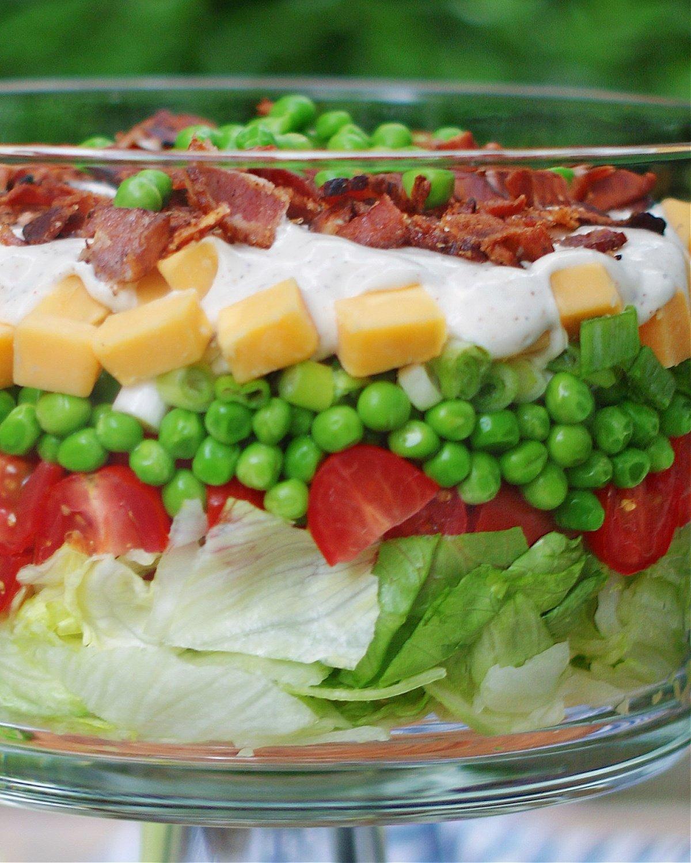 لحم مقدد ، جبنة ، بازلاء ، بصل ، طماطم ، خس وطبقات تتبيلة من السلطة ذات الطبقات.