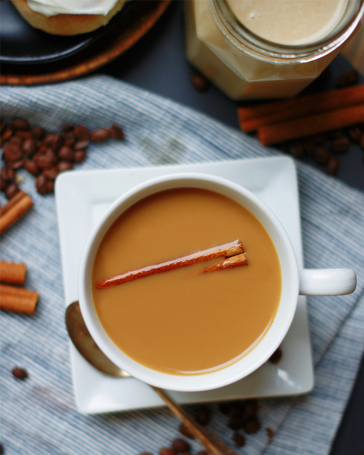 A overhead look into a cup of coffee with homemade cinnamon roll coffee creamer and cinnamon stick