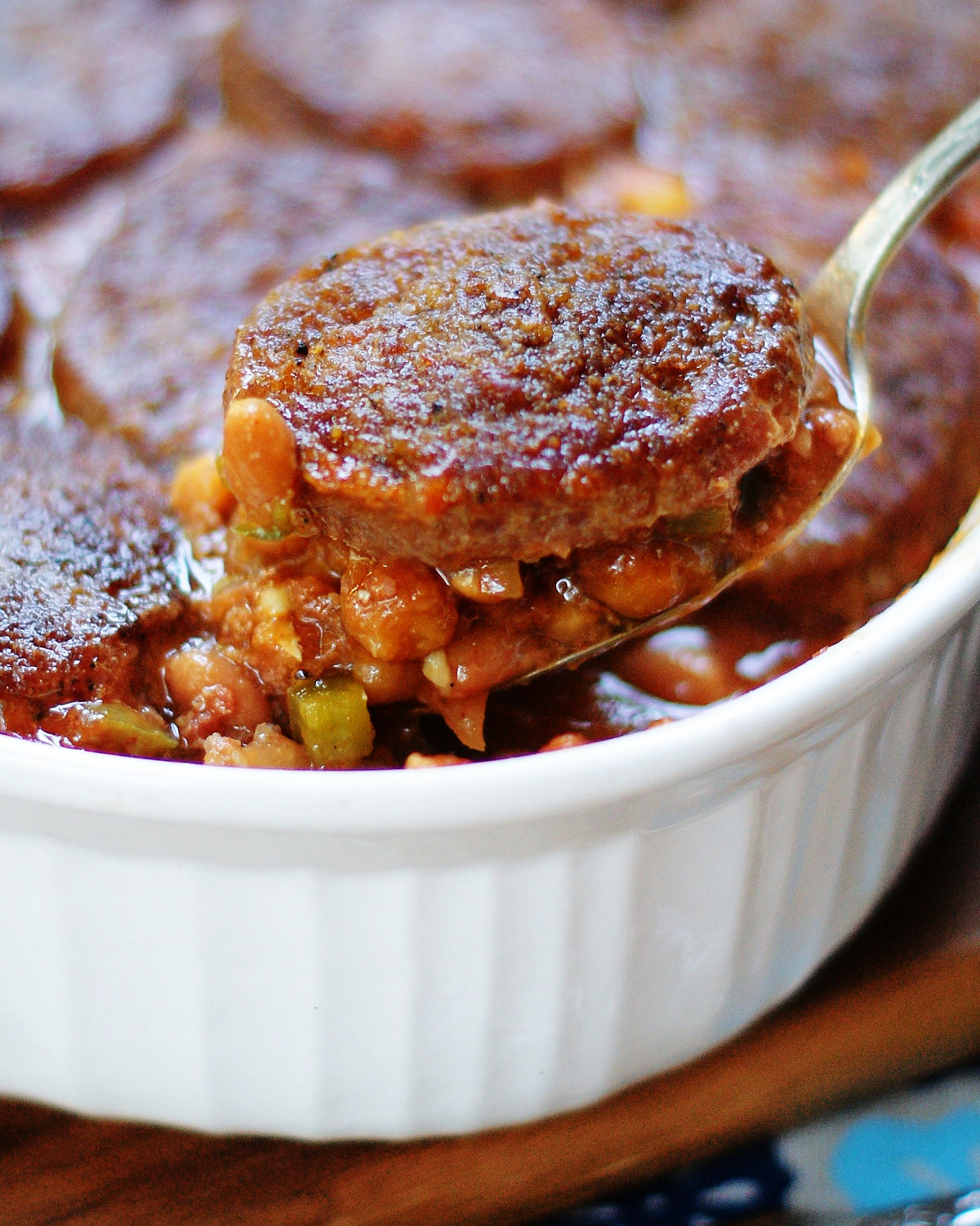 Baked beans with sausage patties on top being served