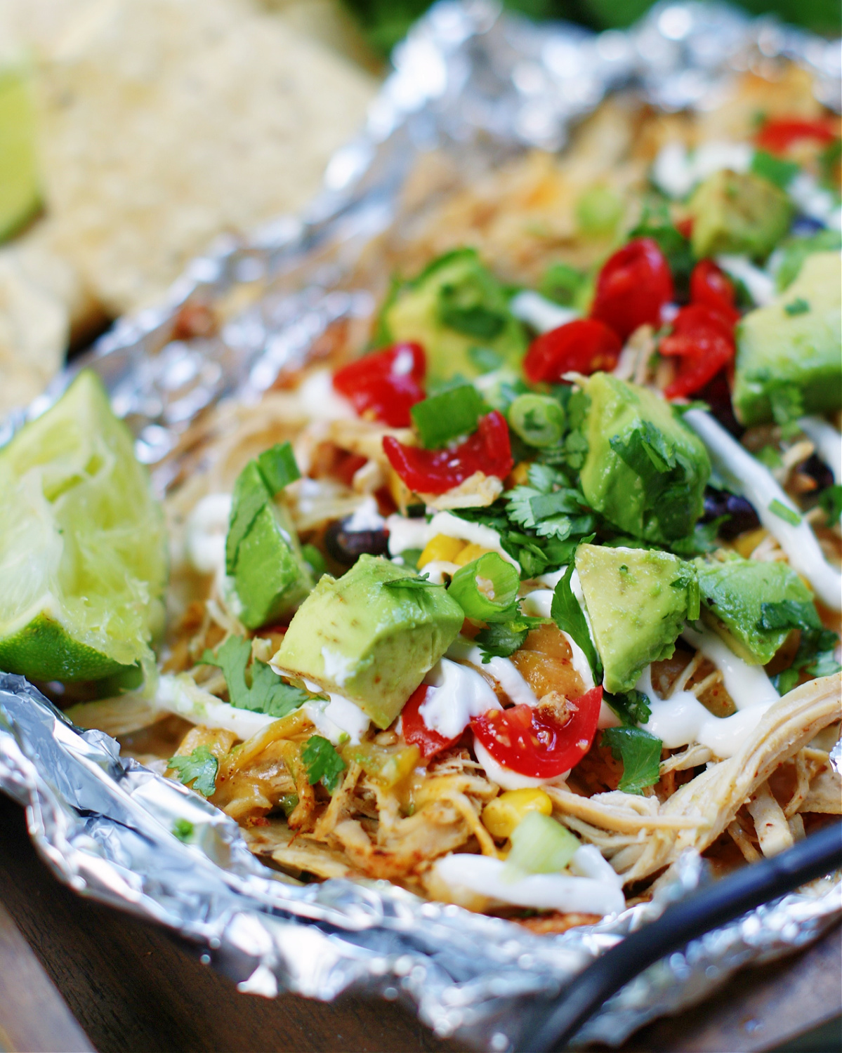 showing the toppings on chicken nachos made in a foil packet