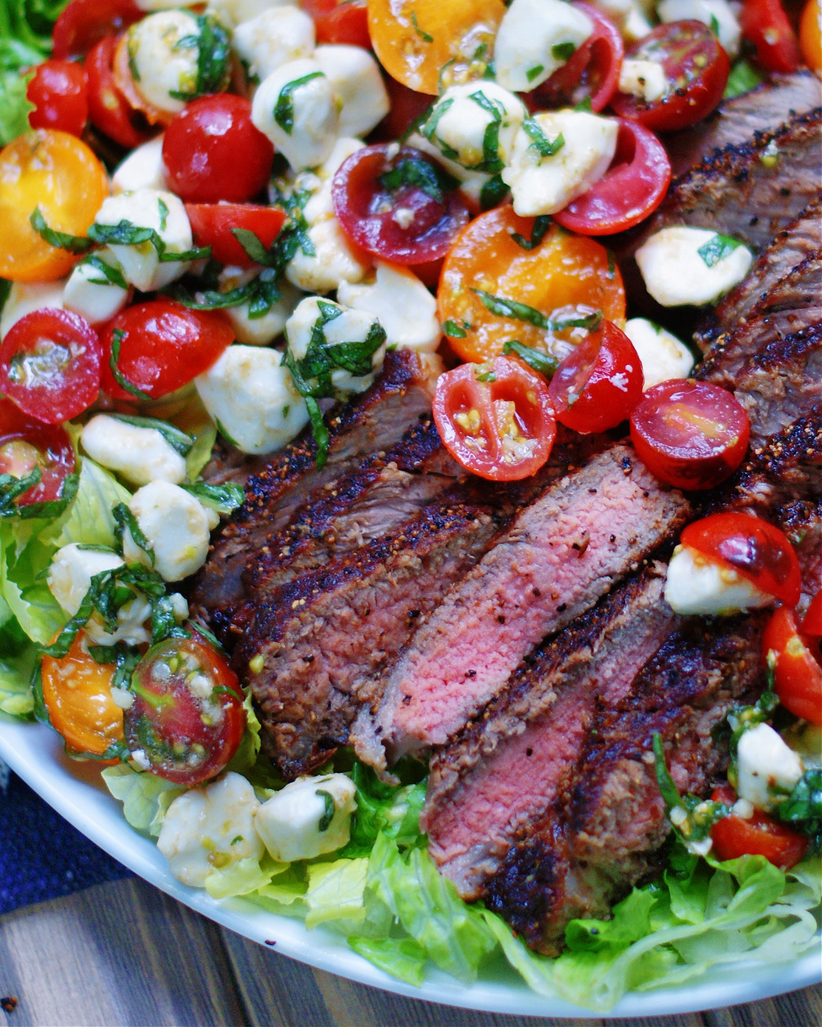 Close up of a caprese salad with steak to show ingredients and texture