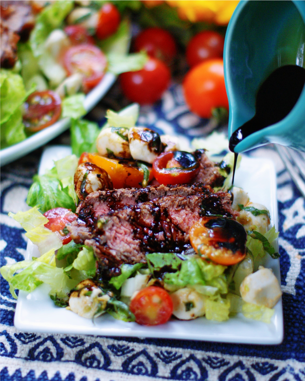 steak caprese salad with a drizzle of balsamic dressing
