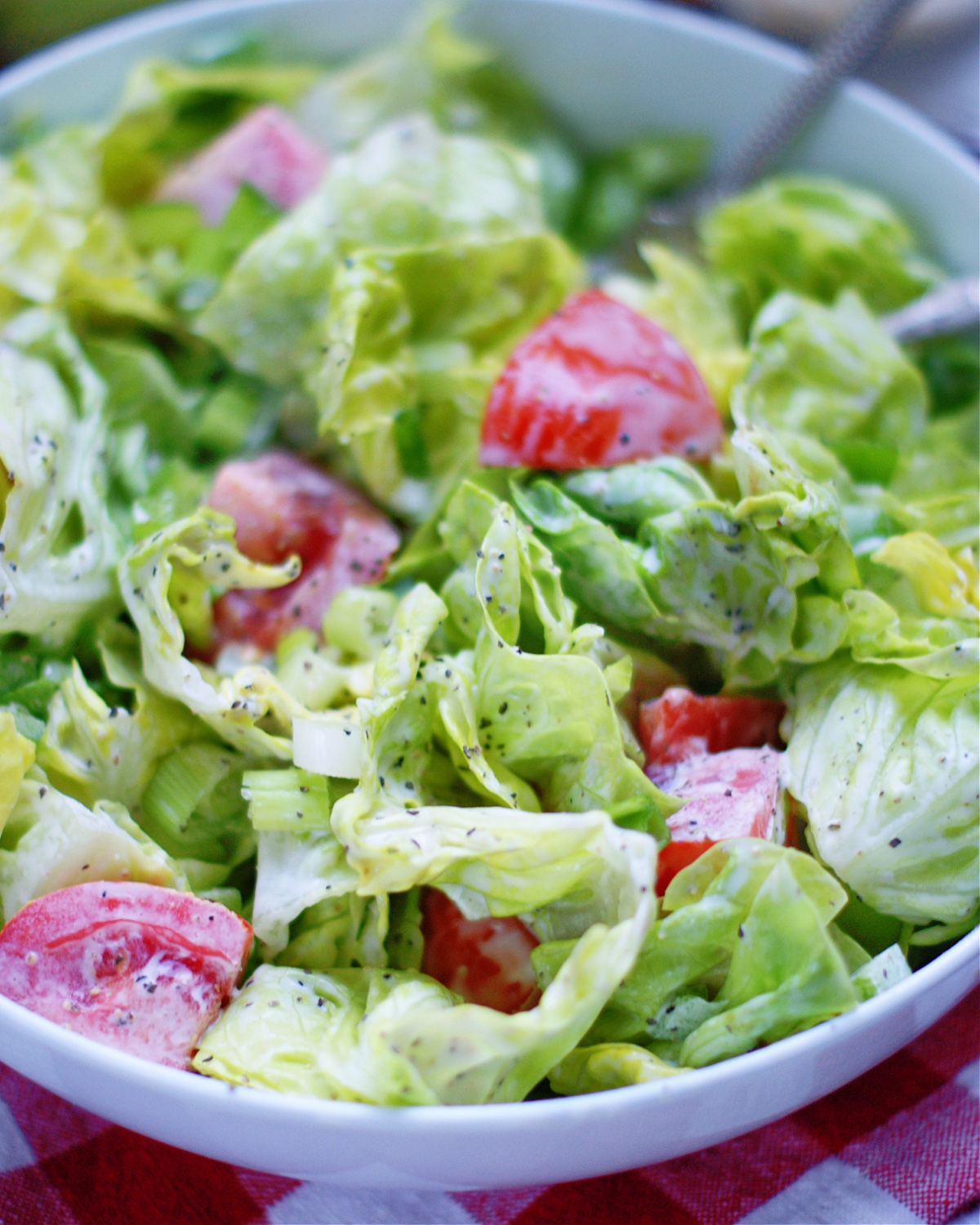 up close of green salad with creamy mayo dressing to show ingredients and texture
