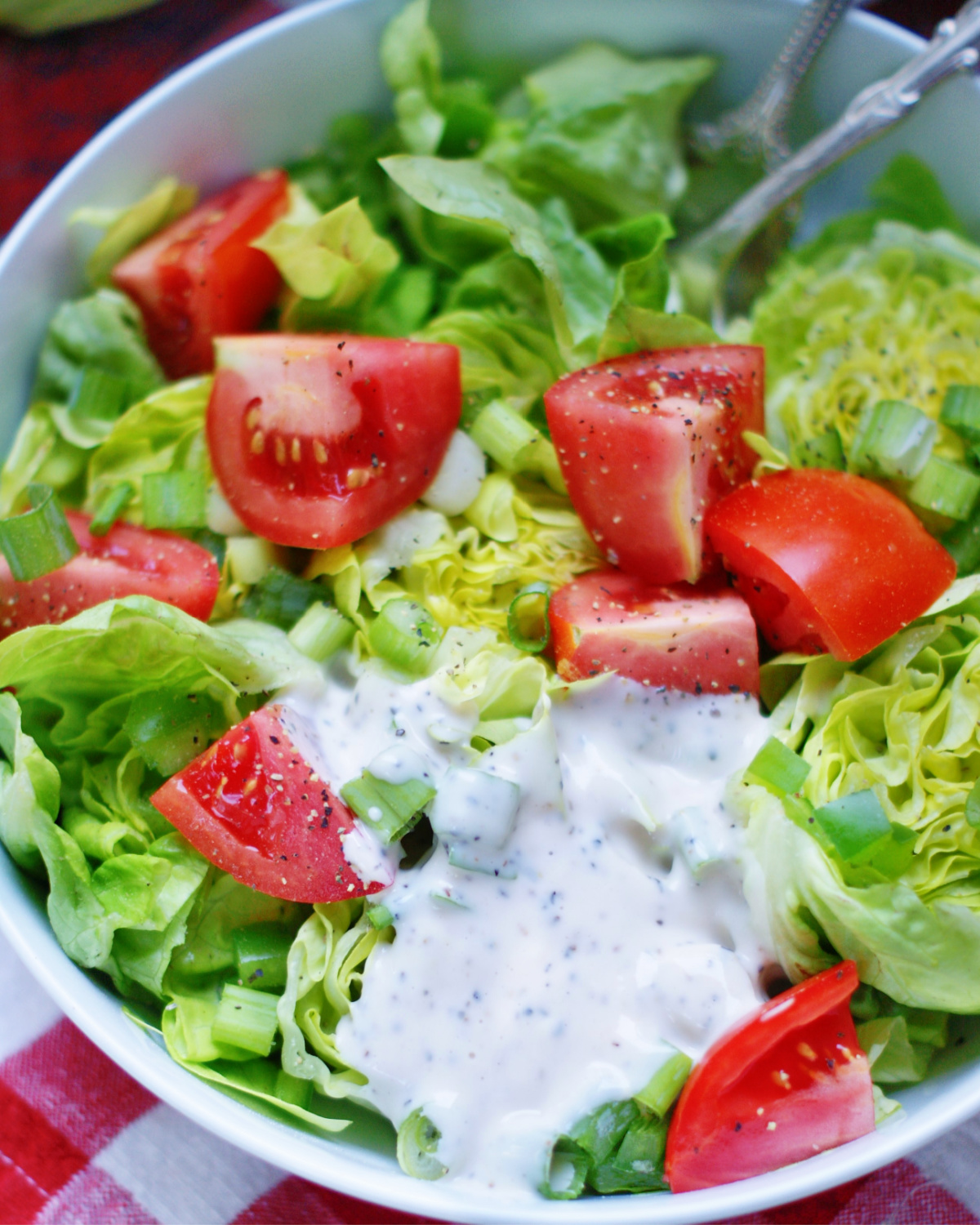 pouring mayo dressing on green salad