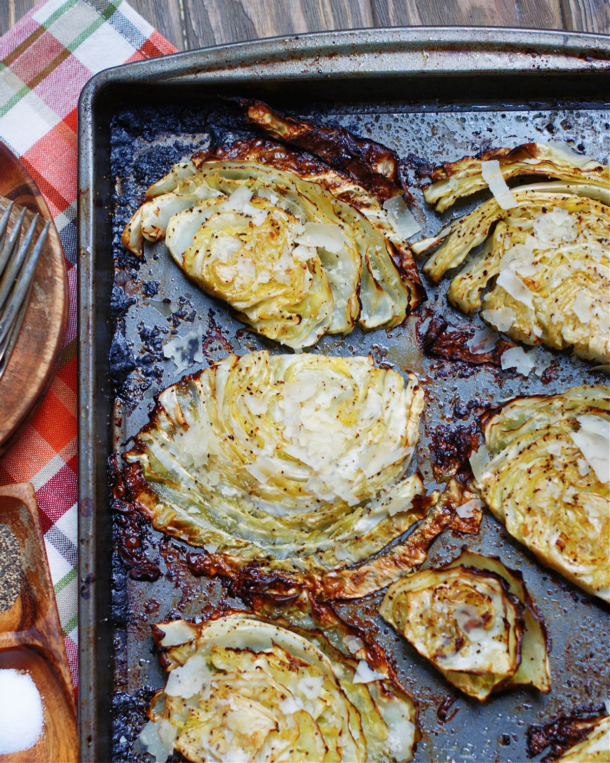 a finished pan of roasted cabbage steaks from the oven with parmesan cheese