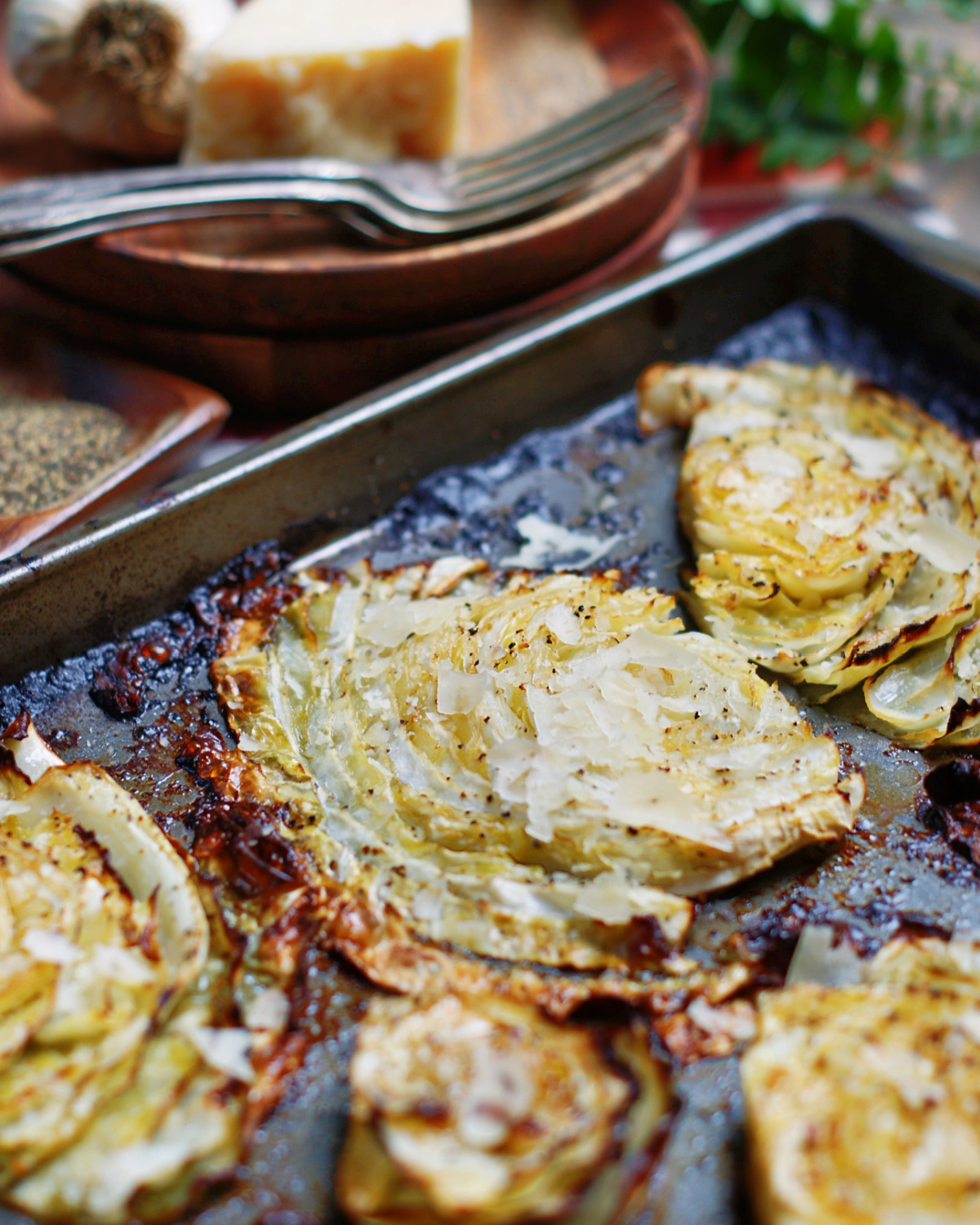 beef flavored roasted cabbage steaks on a sheet pan with parmesan cheese