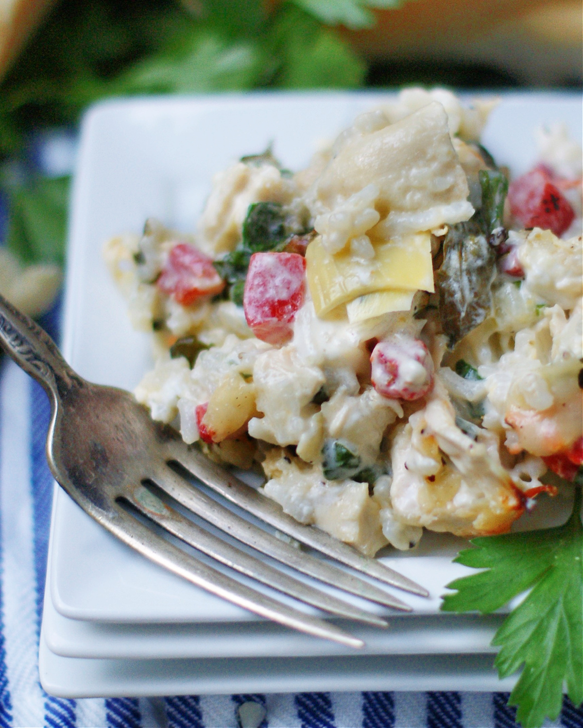 up close of a serving of spinach artichoke chicken casserole to show ingredients and texture